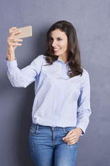 Selfie time. Shot of a smiling young woman taking selfie with her cellphone while standing against a grey wall.