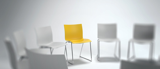 Single yellow chair in a group of white ones