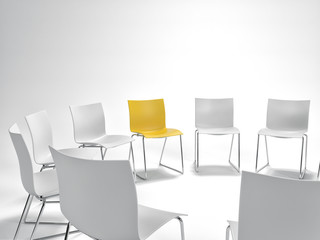 Single yellow chair in a circle of white
