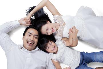 Cheerful family lying in studio
