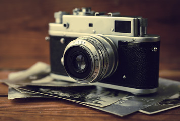 Vintage photo camera with antique pictures on wooden background.