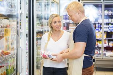 Customer Looking At Salesman Assisting Her In Supermarket