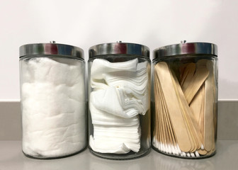 Three glass jars on medical office counter with non-sterile q-tips, tongue depressors, 4x4's and cotton ready for use. Clean, not sterile supplies.