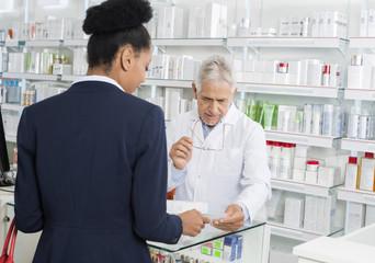 Businesswoman Showing Prescription To Chemist In Pharmacy