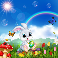 Cartoon rabbit decorating an Easter egg with nature background