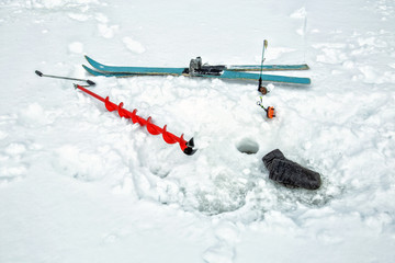 Things of a fisherman in the snow. Mittens, auger, skis and fishing rods