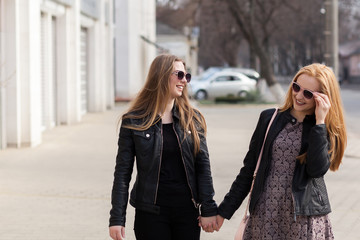 Two female friends in sunglasses having fun outside in the city