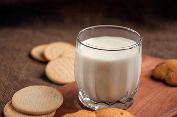 A glass of milk with cookies on a wooden board on a background sacking