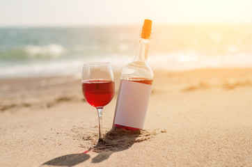 Glass of red rose wine and bottle on the beach at the summer sunny day. Sea on the background
