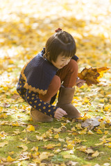 Girl crouching in the midst of Gingko biloba trees
