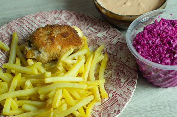 rolled chicken breast filled with paprika, sour cucumber and cheese served with chips, dip and fresh salad