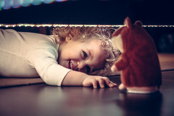 Funny cute smiling baby playing hide and seek under the bed with toy hamster in vintage style