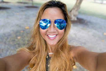 Young girl with blue mirror sunglasses taking selfie from hands with phone