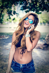 Happy millennial girl in bikini at park talking on smartphone