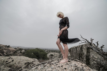 Artistic photo of a blond girl in a transparent black dress walking on the rocks in the field a cloudy day while a branch raises her skirt. The aesthetic is sinister and a little dark.