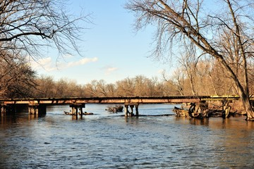 An old railroad bridge crossing the Fox River in Carpentersville, Illinois. The height of the bridge limits the size of boats that can negotiate past this point of the river.