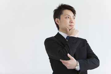 Young businessman with hand on chin