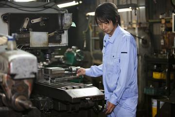 Male Factory Worker Using Machine