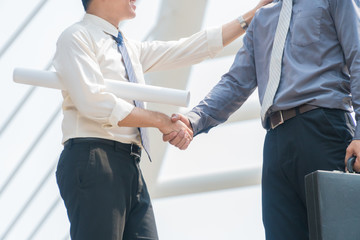 Asian businessmen shaking hands with with success gesture in modern city. Focus hand