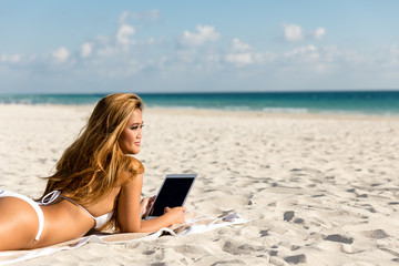 Attractive woman lying down on beach by the ocean using a tablet computer