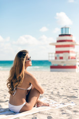 Beautiful woman sitting on beach looking at the ocean