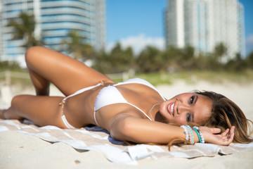 Sexy fit asian woman in white bikini lies on the beach posing