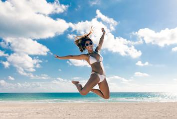Happy bikini asian woman jumping of joy on beach. Tropical vacation travel destination.