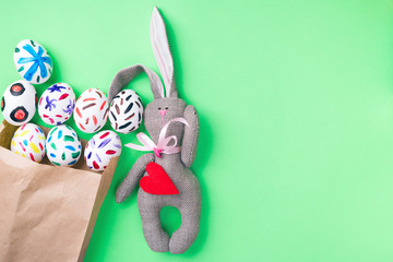 Easter eggs in a paper bag. Green background. Easter bunny. Rabbit. Easter ideas. Easter eggs. Space for text.