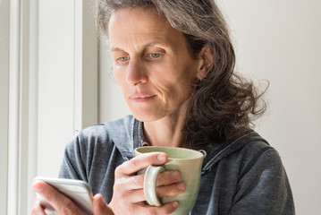 Natural looking middle aged woman looking at smart phone and holding green cup (selective focus)