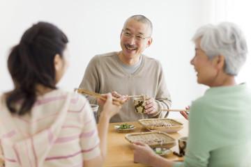 Family eating soba noodles, smiling