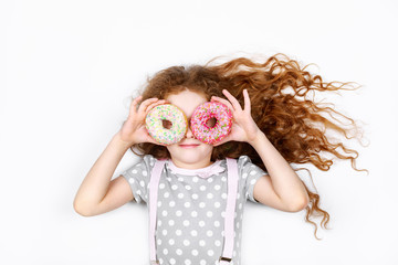 Little girl having fun with donuts eyes.