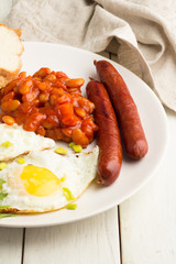 Fried eggs, beans, grilled sausages, bread on a plate on a white wooden background close-up.