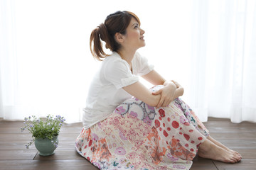 Young woman sitting on floor and looking up