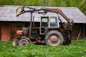 Old rusty tractor with dragging bucket