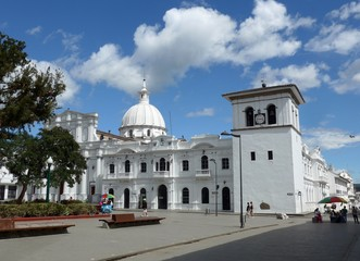 A blue sky day above the beautiful large white Torre del Reloj in the central plaza of Popayan