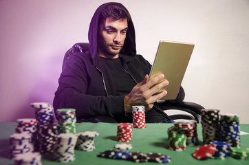 Poker player playing online via tablet at home/poker addiction