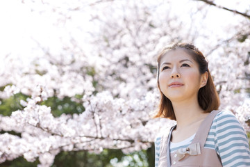 Young woman standing in front of cherry blossom tree