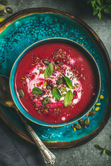 Spring detox beetroot soup with mint, chia, flax and pumpkin seeds in blue ceramic bowl over grey concrete background, top view. Dieting, clean eating, weight loss, vegan, vegetarian food concept