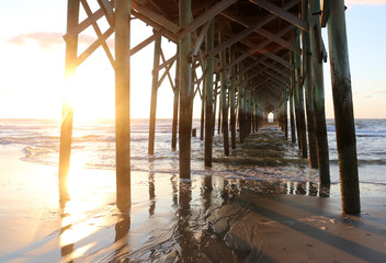 Atlantic ocean sunrise background. Sunrise over the ocean. Atlantic ocean landscape with a sun and clouds reflected in shallow water and wooden pier in Myrtle Beach area, South Carolina, USA.