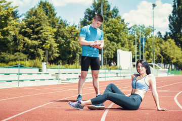 Girl on track with her personal trainer.