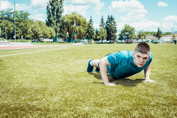 Young man doing push ups outdoor in grass.