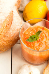 Gazpacho, bread with pesto and vegetables close-up on a white background.