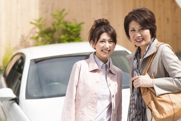 Portrait of young woman and senior woman standing by car, smiling