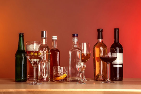 Table with different bottles of wine and spirits on color background