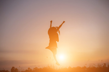 A cheerful woman jumps at the sun.