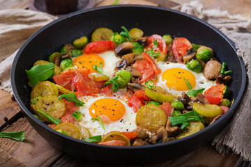 Breakfast for two. Fried eggs with vegetables - shakshuka in a frying pan on a wooden background in rustic style.