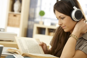 Side view of reading woman with headphones