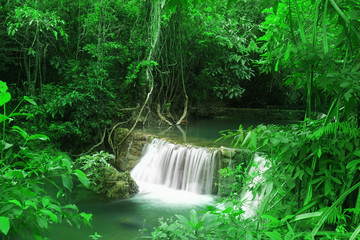 waterfall with clear green water and rock for relax with tree and root in the jungle at Huay Mae Khamin waterfall for nature landscape and background