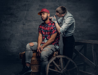 Caucasian male cutting the beard of Black hipster males.