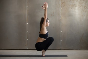 Young attractive woman practicing yoga, siting in Utkatasana exercise, Squat, Chair pose, working out, wearing black sportswear, cool urban style, full length, grey studio background, side view
